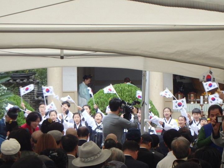 Some cute kids singing some songs and waving Taegukgi