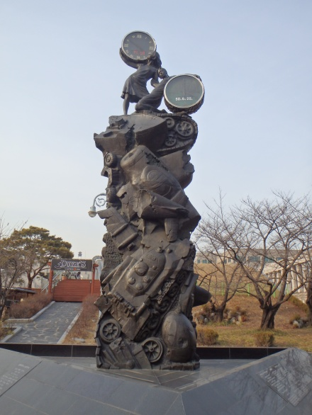 The Clock Tower of Peace Each girl holds a clock. One displays the current time and the other displays the date and time the Korean War began